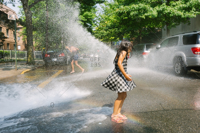 Brooklyn, New York, USA - July 8, 2016: Girl sprayed by water in street