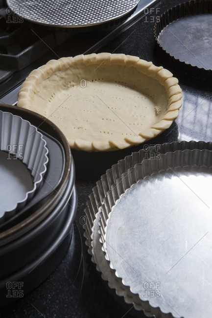 Pie Crust in Pan Near Other Empty Pie Pans