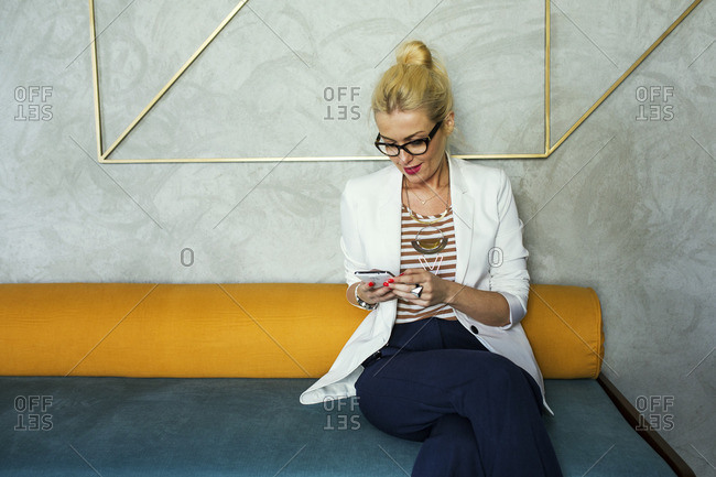 Smiling businesswoman using smart phone while sitting on sofa at hotel lobby