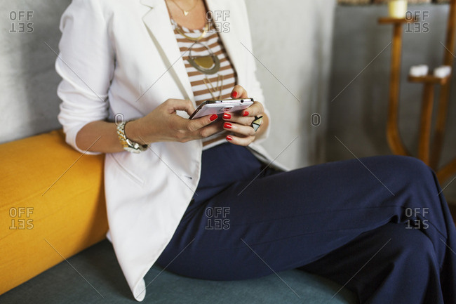 Midsection of creative businesswoman using smart phone in hotel lobby