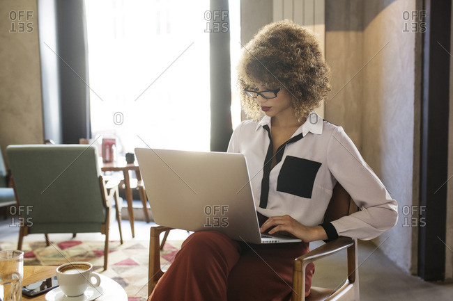 Businesswoman using laptop in hotel lobby
