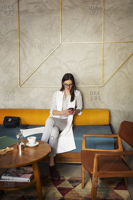 Smiling businesswoman using smart phone while sitting on sofa in hotel lobby