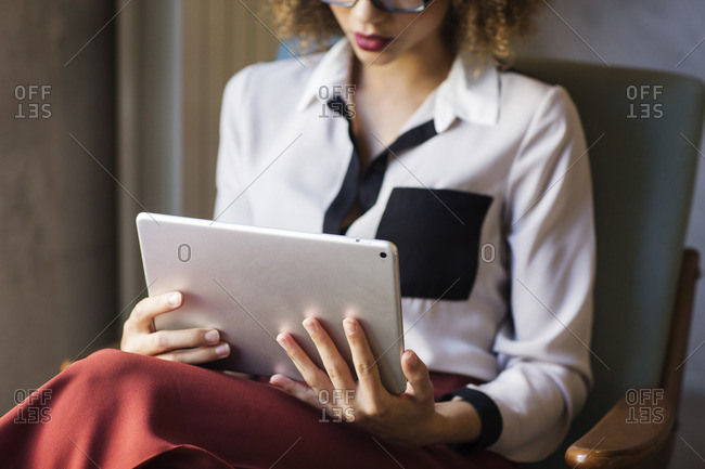 Midsection of businesswoman using tablet computer at hotel lobby