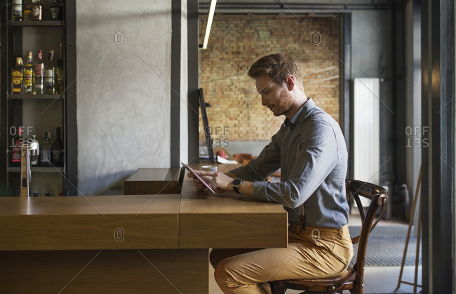 Businessman using tablet computer while sitting at bar counter in hotel