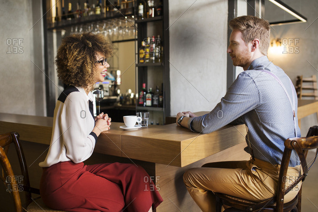 Happy businesswoman talking to male colleague at bar counter in hotel