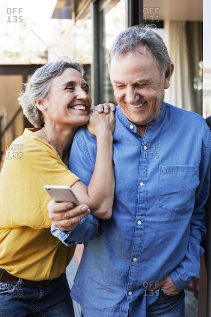 Cheerful woman looking at senior man using smart phone on porch