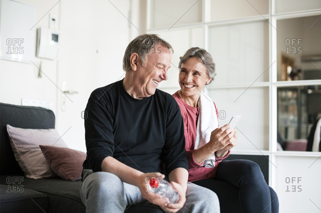 Happy senior couple using smart phone in living room
