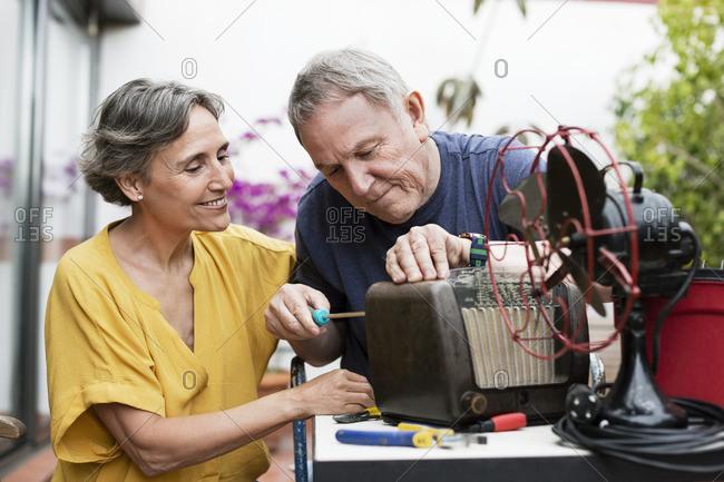 Senior couple repairing old-fashioned radio at yard