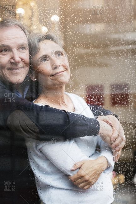 Loving senior couple looking through wet window