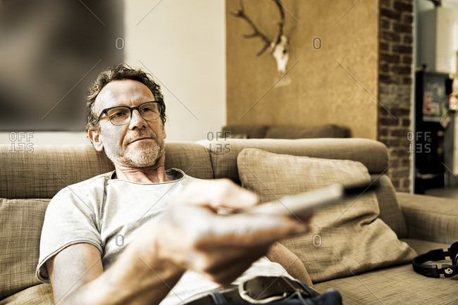Portrait of man lying on the couch using remote control