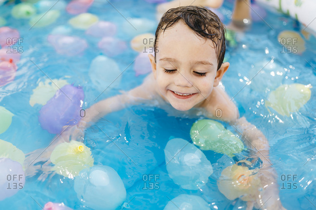 Smiling little boy playing with waterballoons in the pool