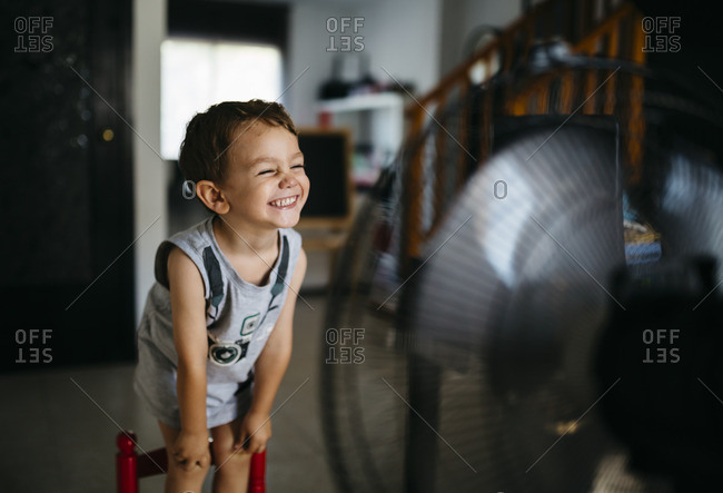 Grinning little boy standing in front of ventilator