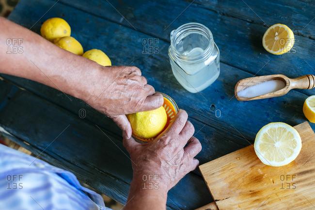 Close-up of hands squeezing lemons to make lemonade