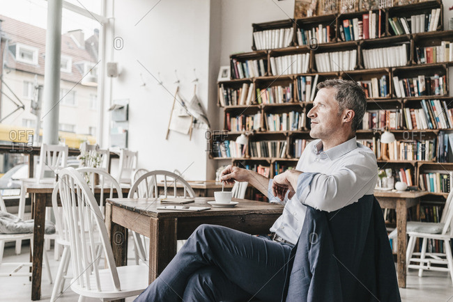Businessman in cafe drinking coffee- daydreaming
