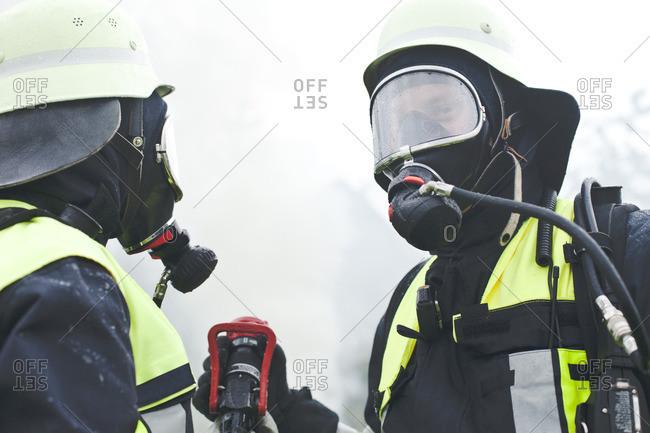 Two firefighters wearing oxygen masks