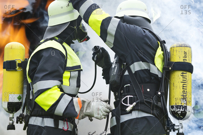 Two firefighters preparing operation - Offset