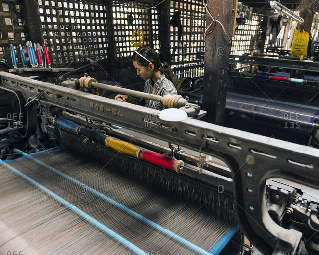 Mandalay, Myanmar - February 4, 2014: Asian woman working in a traditional textiles factory using old fashioned machinery