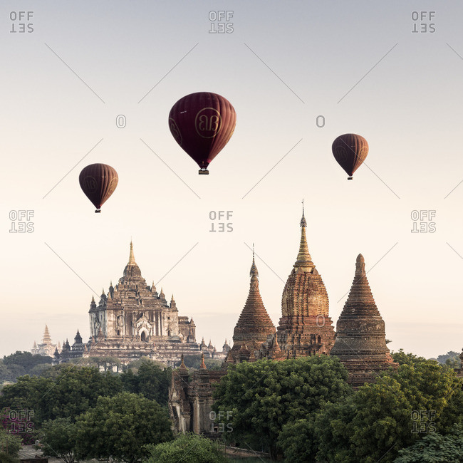 Bagan, Myanmar - December 12, 2013: View of the ancient temples of Bagan, with hot air balloons carrying tourists on sightseeing tour
