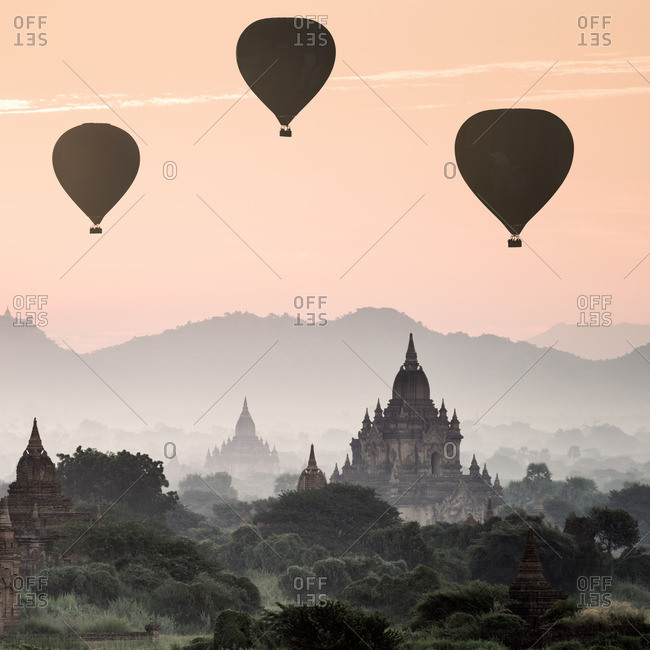 Bagan, Myanmar - December 12, 2013: Silhouette of hot air balloons flying over the ancient temples of Bagan, Myanmar