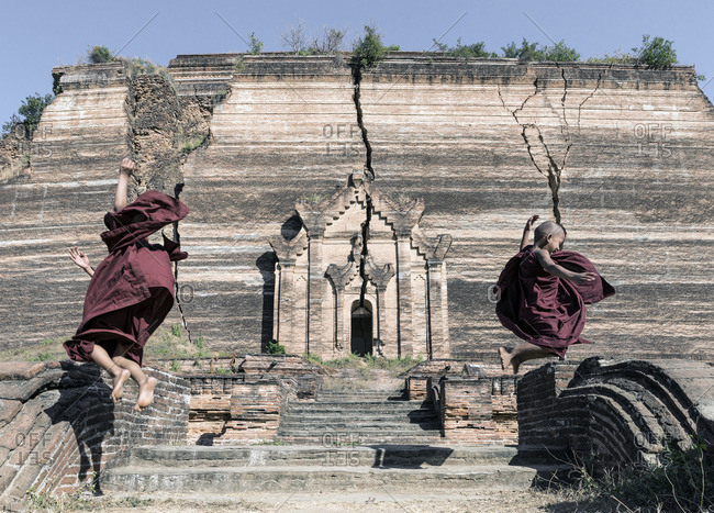 Young novice Buddhist monks jumping off of wall in front of Mingun Paya temple