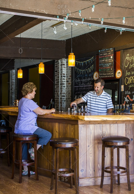 Snohomish, WA - July 30, 2015: A man pours a tasting of liquor at a distillery in Snohomish, WA