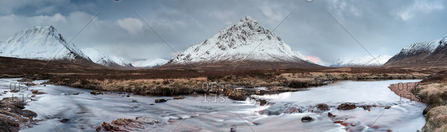 Panoramic winter vista of mountains and river in Glencoe, Scotland