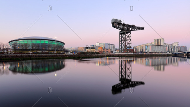 Sports arena and crane on the River Clyde waterfront at dusk, Glasgow Scotland