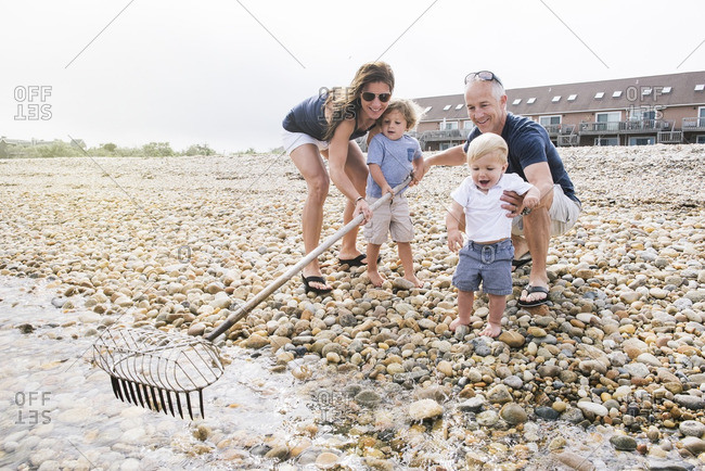 Family of four with beach rake