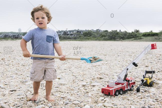 Boy holding sand shovel on beach