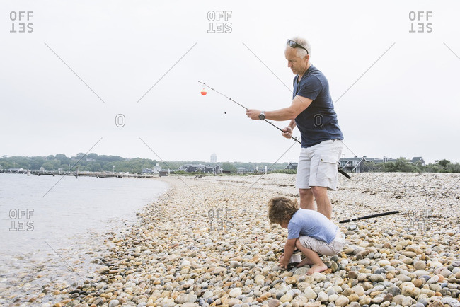 Boy and man beach fishing