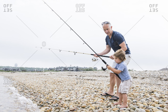 Man helping boy fish on beach