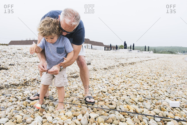 Dad helping boy bait fishing pole