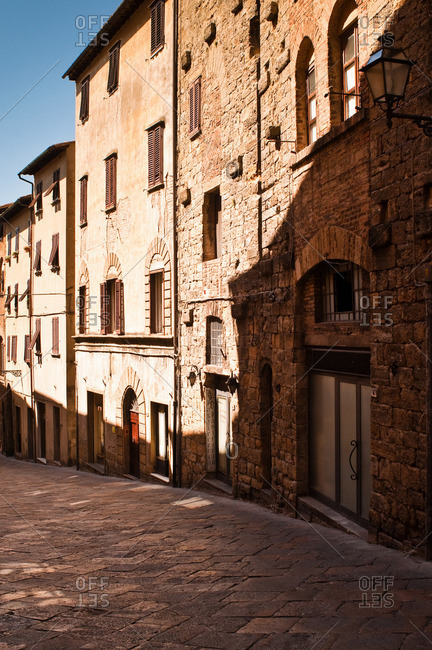 Volterra, Italy - October 26, 2011: Shadow buildings on historic walled hill town