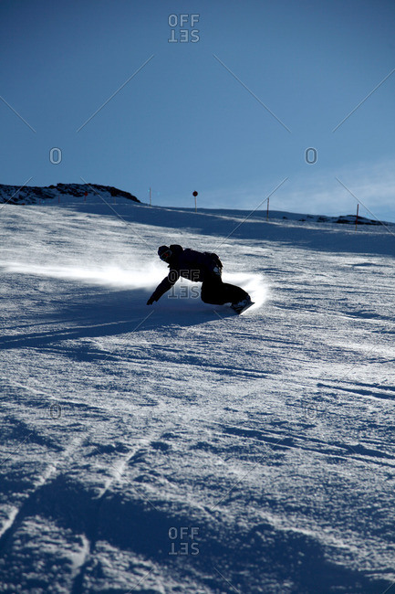 Male snowboarder sliding down ski slope