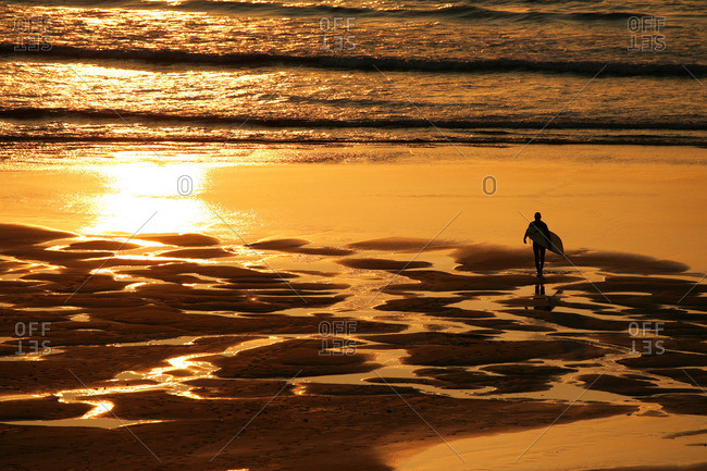 Surfer on beach in Cornwall, UK