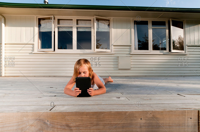 Girl on porch, reading electronic book