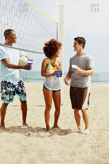 Friends on beach with volleyball and net