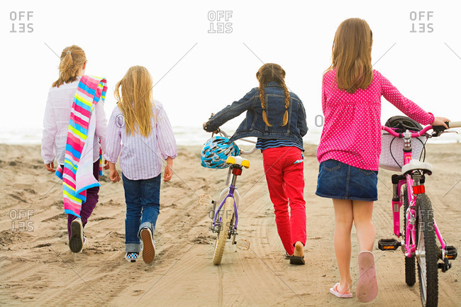 Girls walking over sand at beach