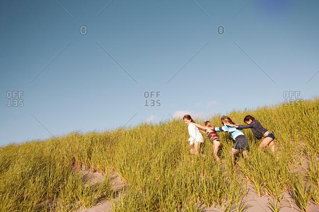Girls walking in a line through long grass at beach