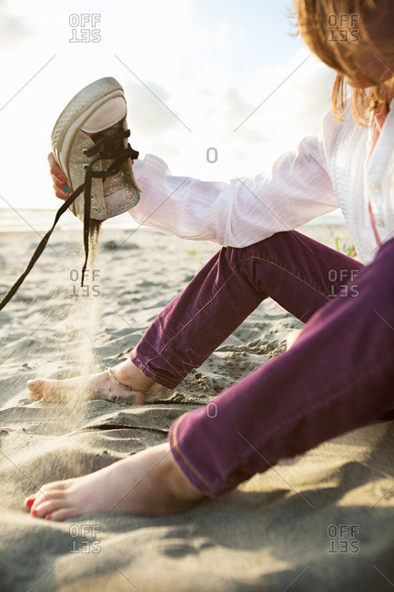 Girl emptying shoe at beach