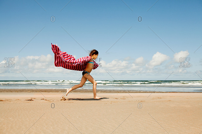 Girl running with blanket at beach