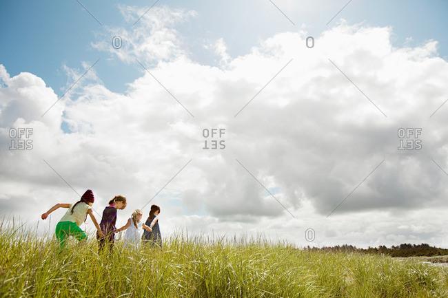 Girls walking through long grass
