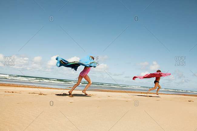 Girls running with blankets at beach
