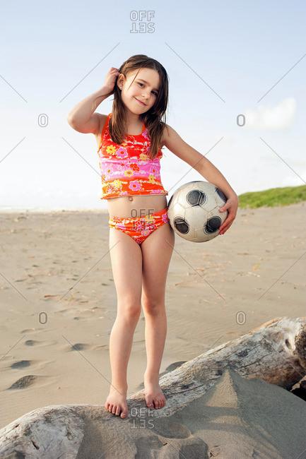 Girl holding soccer ball at beach