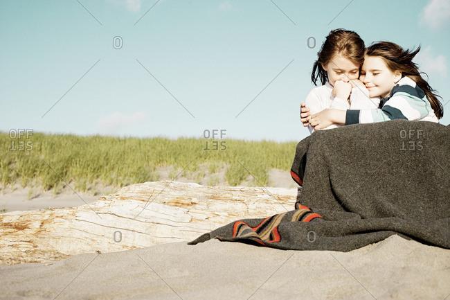 Girls hugging in blanket at beach