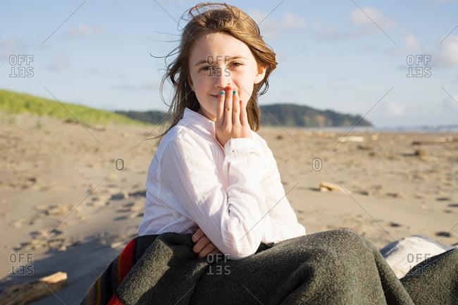 Girl sitting in blanket at beach
