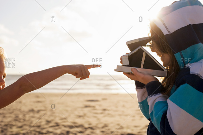 Girl pointing at friend with instant camera at beach