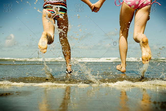 Two girls holding hands running into sea
