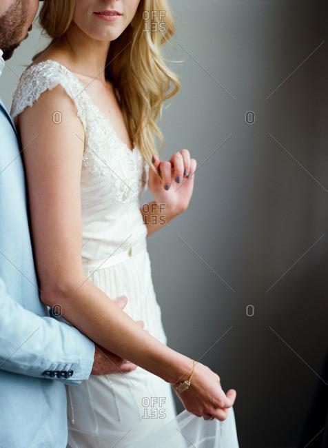 Portrait of romantic groom embracing bride in white dress
