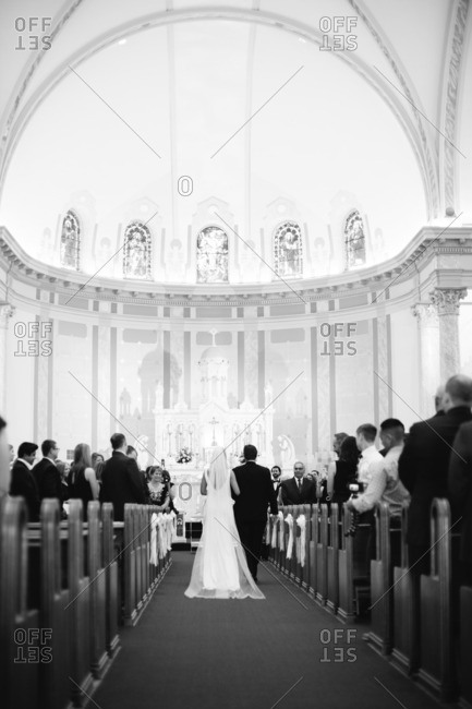 Bride being escorted down aisle of church to alter